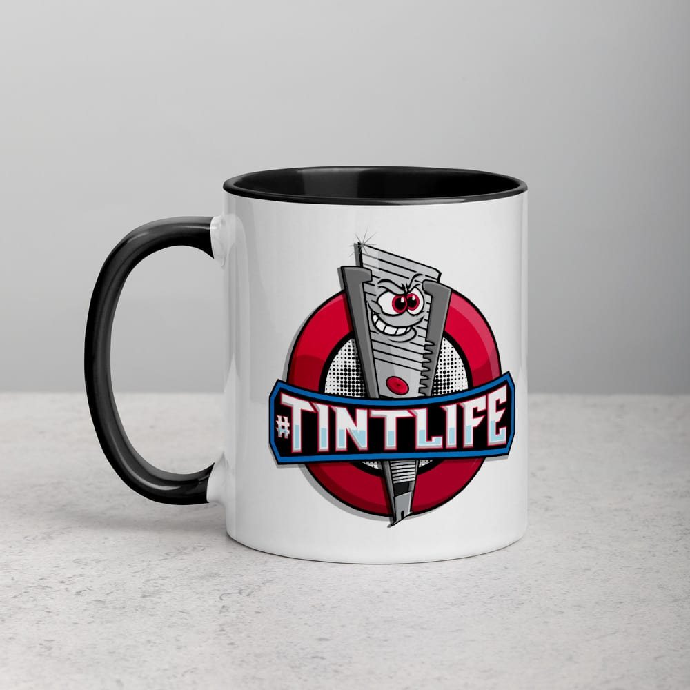 A white ceramic coffee mug with a black handle and interior featuring the Red Dot caricature knife and #TintLife.