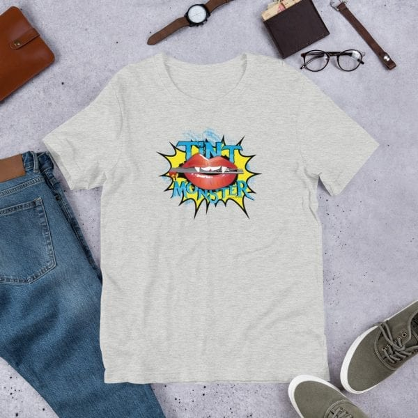 An athletic heather pre-shrunk, 52% combed and ring-spun cotton and 48% polyester blend t-shirt with a unisex cut flattering for both men and women featuring the Tint Monster logo by Kari Yochum