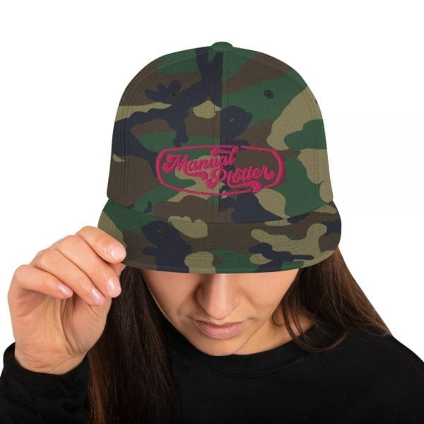 Green Camo Snapback style baseball cap featuring the Manual Plotter logo from Kari Yochum in pink lettering