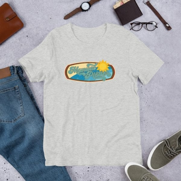 An athletic heather pre-shrunk, 52% combed and ring-spun cotton and 48% polyester blend t-shirt with a unisex cut flattering for both men and women featuring the Manual Plotter - Beach Edition logo by Kari Yochum