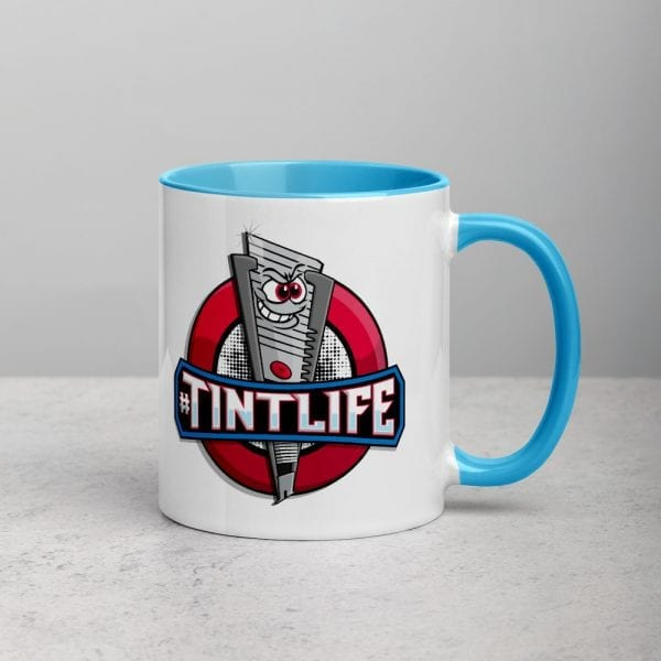 A white ceramic coffee mug with a blue handle and interior featuring the Red Dot caricature knife and #TintLife.
