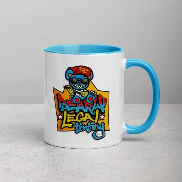A white ceramic coffee mug with a blue handle and interior featuring the Bearly Legal Tinting – Graffiti logo by Kari Yochum