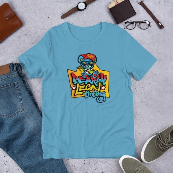 An ocean blue pre-shrunk, 100% combed and ring-spun cotton t-shirt with a unisex cut flattering for both men and women featuring the Bearly Legal Tinting - Graffiti logo by Kari Yochum