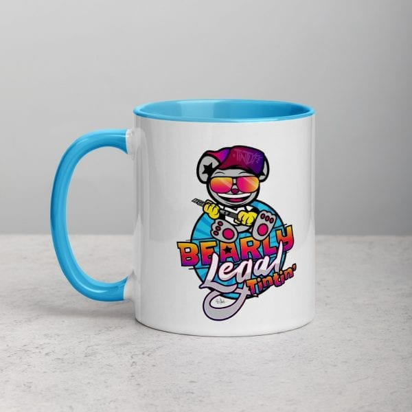 A white ceramic coffee mug with a blue handle and interior featuring the Bearly Legal Tintin' logo by Kari Yochum